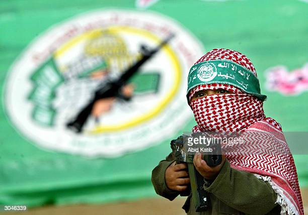A masked Palestinian boy demonstrates martial arts maneuvers with a plastic gun March 5 2004 in the AlBureij refugee camp in the Gaza Strip The...