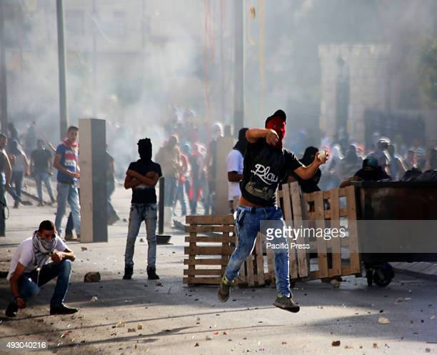 A masked Palestinian demonstrator hurls a rock towards the Israeli military checkpoint in Bethlehem West Bank Across all West Bank cities in the...