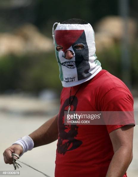 A masked Palestinian demonstrator prepares to throw stones with his slingshot during clashes with members of the Israeli security forces outside the...