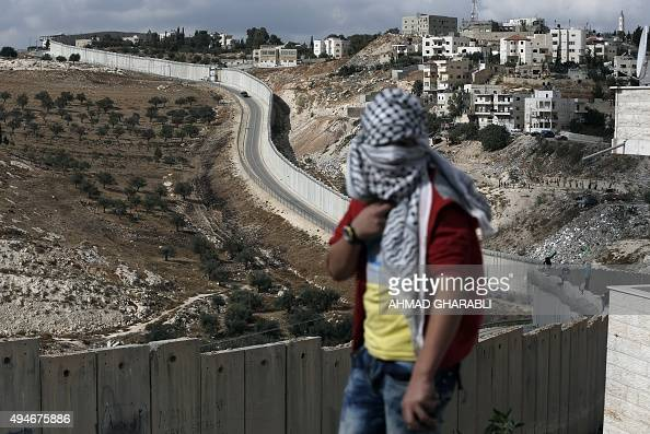 A masked Palestinian demonstrator protests near the Israeli controvertial separation wall separating the West Bank city of Abu Dis from east...