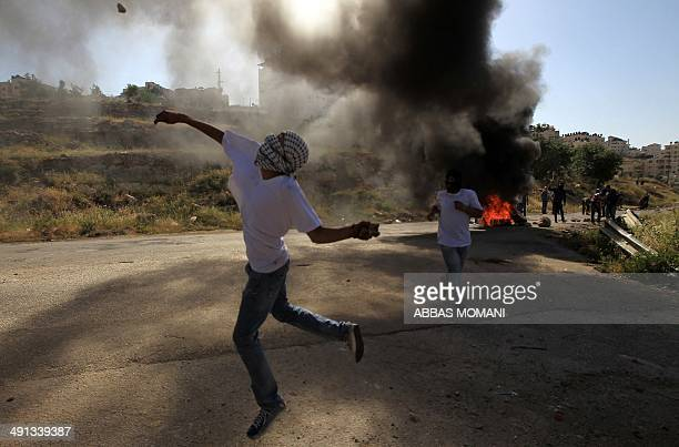 A masked Palestinian demonstrator throws a stone during clashes with members of the Israeli security forces outside the Israelirun Ofer prison in the...