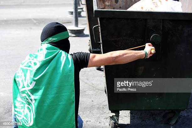 A masked Palestinian demonstrator uses a slingshot against Israeli soldiers during demonstrations in the West Bank city of Bethlehem Across all West...
