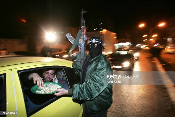 A masked Palestinian fighter from The Popular Resistance Committees distributes sweets to drivers as he celebrates after Israeli Prime Minister Ariel...
