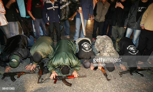 Masked Palestinian fighters from The Popular Resistance Committees pray to thank God after Israeli Prime Minister Ariel Sharon suffered a stroke and...