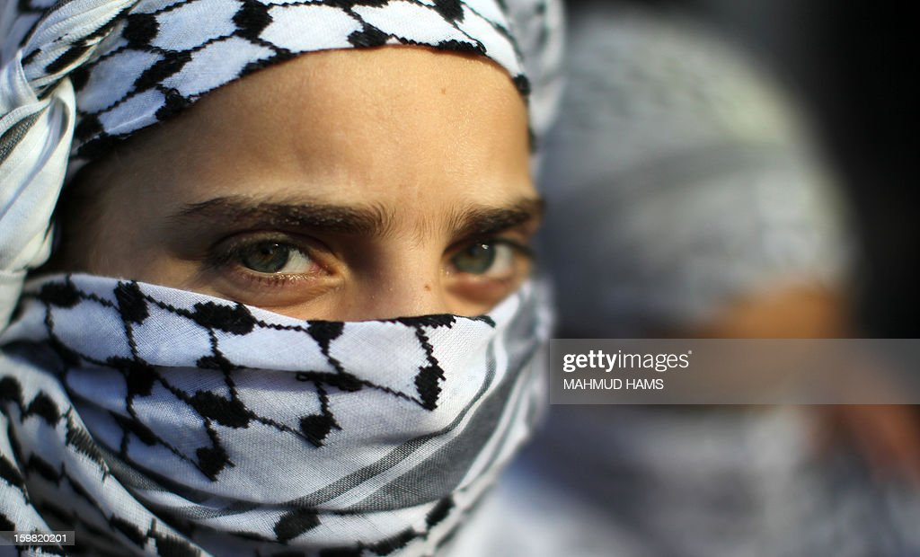 A masked Palestinian girl attends a protest calling for the release of Palestinian prisoners from Israeli jails outside the International Red Cross offices in Gaza City on January 21, 2013.