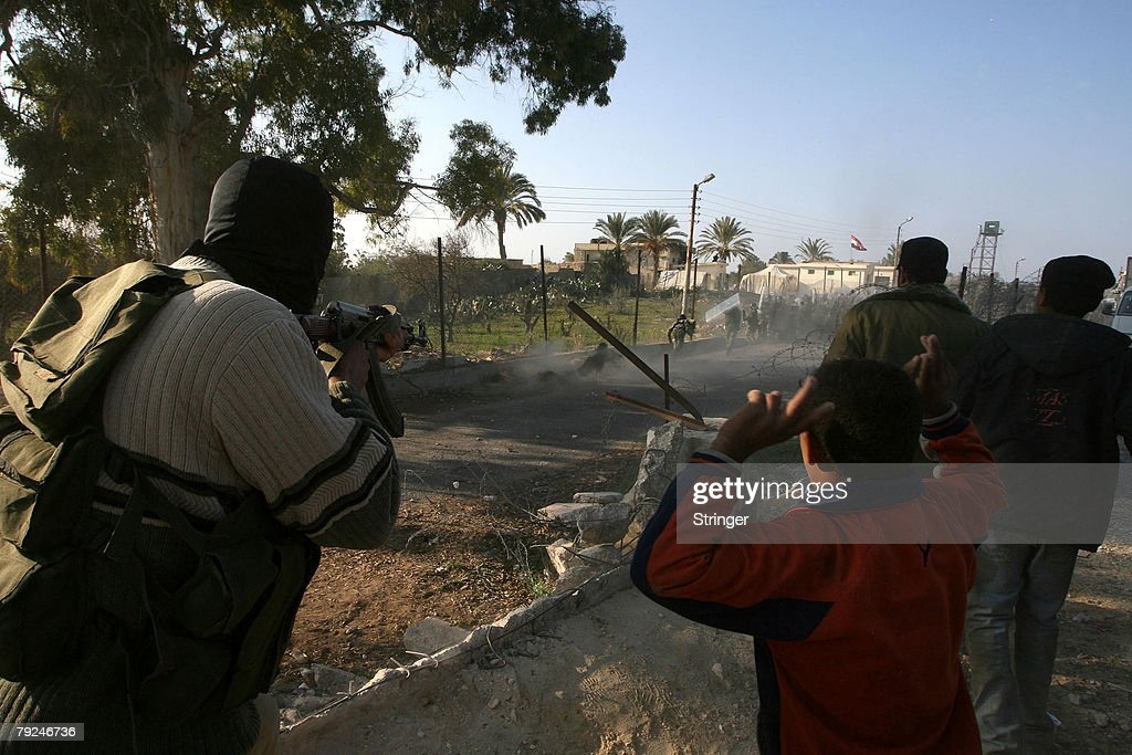 A masked Palestinian gunman opens fire towards Egyptian riot policemen as a bulldozer was used to destroy a section of the border wall between the Gaza Strip and Egypt January 25, 2008 in the town of Rafah, in the southern Gaza Strip. Militants open up new breaches on the border with Egypt after Egyptian security forces tried to retake control of the border and stop Palestinians from entering Egypt.