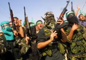 Masked Palestinian Hamas militants attend the funeral of Tariq Abu Hussein senior Gaza field commander of the Ezzedin alQassam Brigades the armed...