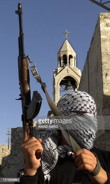 A masked Palestinian holds a Kalashnikov rifle in front of the Church of Nativity in the West Bank town of Bethlehem during a rally 01 January 2001...