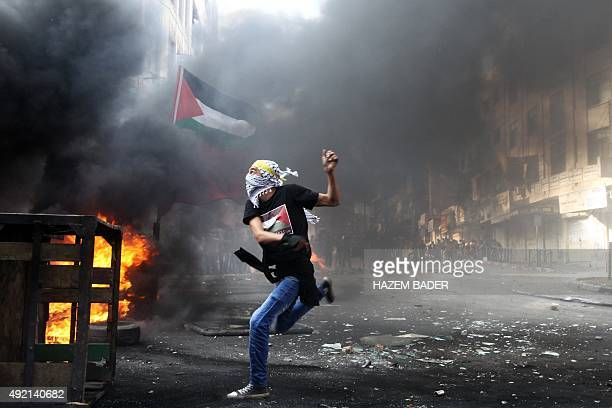 A masked Palestinian hurls rocks towards Israeli soldiers during clashes following the funeral of Mohammed Fares alJaabari on October 10 in the...