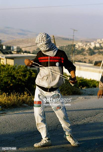 A masked Palestinian man carries a sling used to fling rocks during a riot in Shufat Jerusalem The riot is in response to a shooting by a discharged...