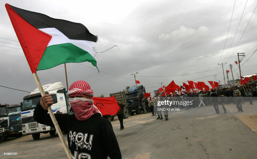 A masked Palestinian man waves his national flag as he leads protestors during a demonstration organised by the Democratic Front for the Liberation...