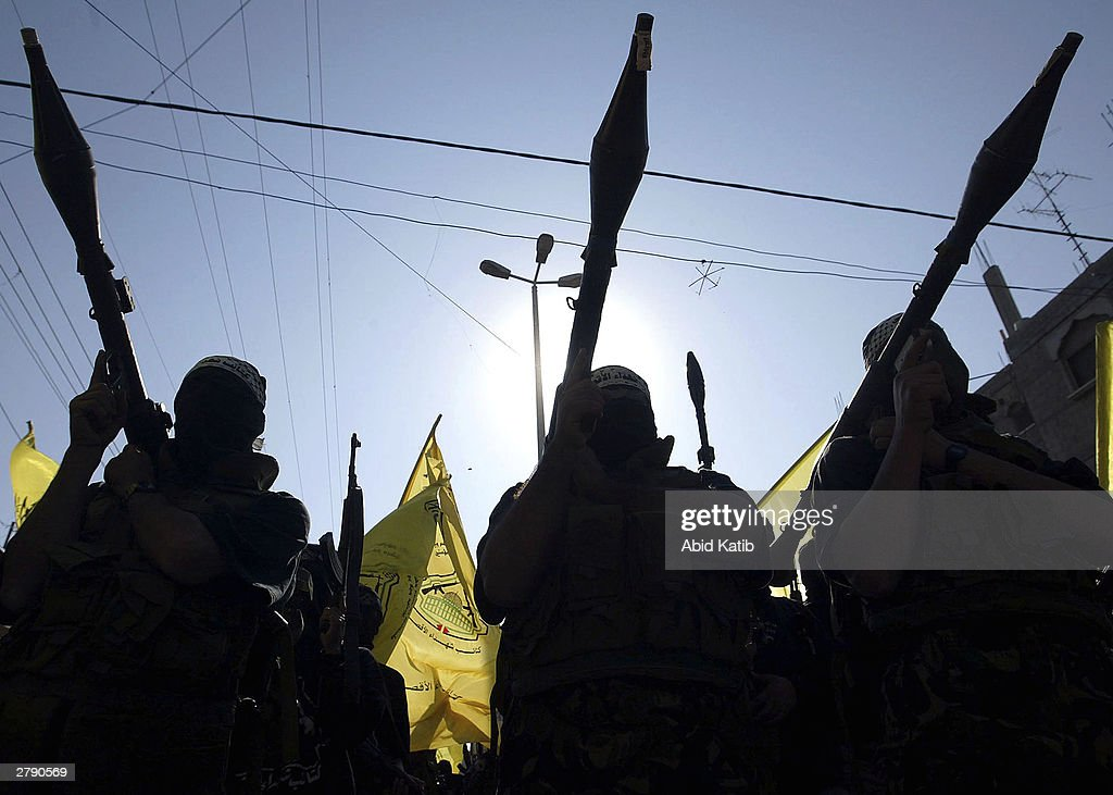 Masked Palestinian members of the AlAqsa Martyrs Brigades a militant group linked to Palestinian leader Yasser Arafat's Fatah movement carry their...