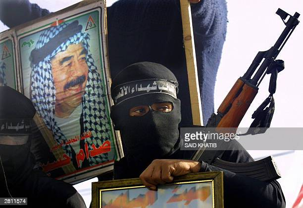 A masked Palestinian militant holds his weapon next to a portrait of former Iraqi leader Saddam Hussein during a demonstration in the Gaza Strip town...