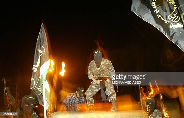 Masked Palestinian militants from the AlQuds Brigades the military wing of the Islamic Jihad demonstrate along a street of the Khan Yunes refugee...