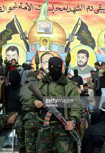 Masked Palestinian militants from the Islamic Jihad group show off their weapons during a rally in support of Mekled Hameid the leader of their...
