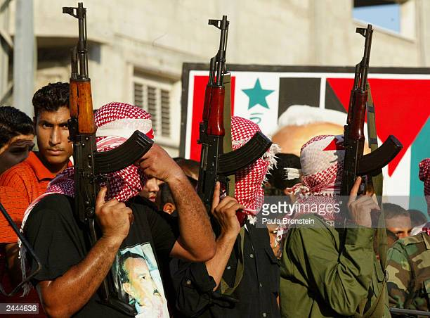 Masked Palestinian militants hold AK47 guns during a rally at Boreji refugee camp on August 29 2003 in Gaza Strip Gaza City The Palestinian militant...