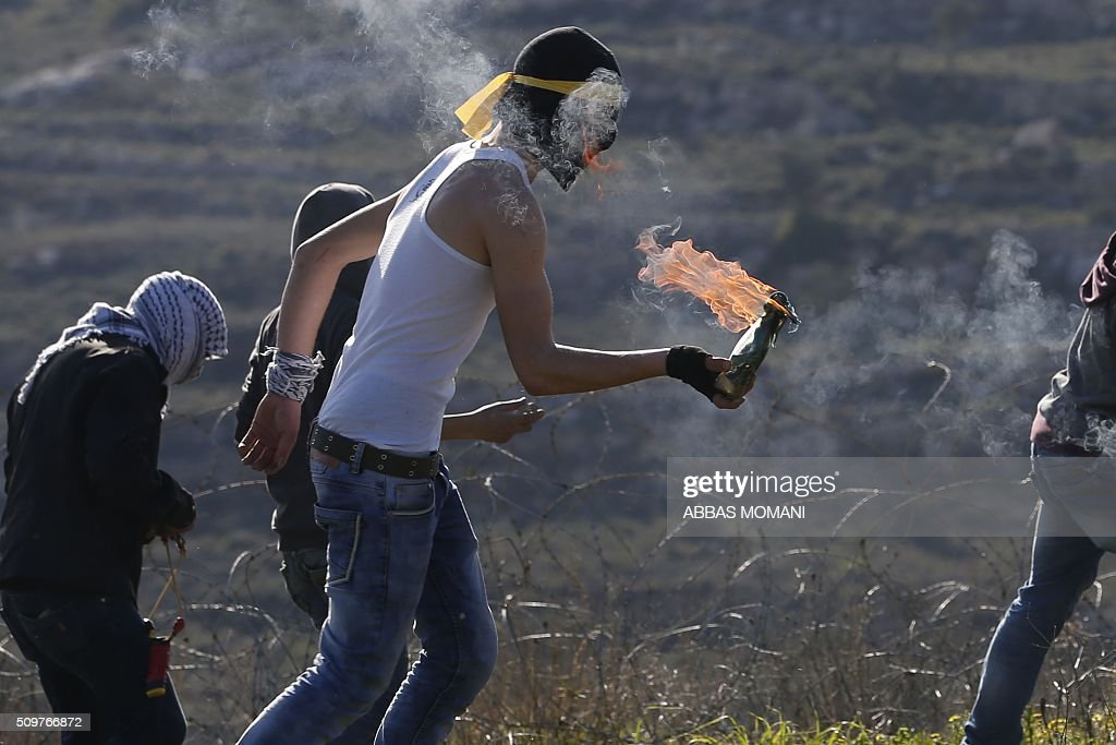 A masked Palestinian protester holds a burning molotov cocktail during clashes with Israeli forces following a demonstration on February 12, 2016 in solidarity with Palestinian prisoners held in Israeli jails, outside the compound of the Israeli-run Ofer Prison near Betunia in the occoupied West Bank. / AFP / ABBAS MOMANI / AFP / ABBAS MOMANI