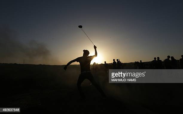 A masked Palestinian protester hurls a stone towards Israeli troops during clashes near a border fence between Israel and the Gaza Strip n October 14...