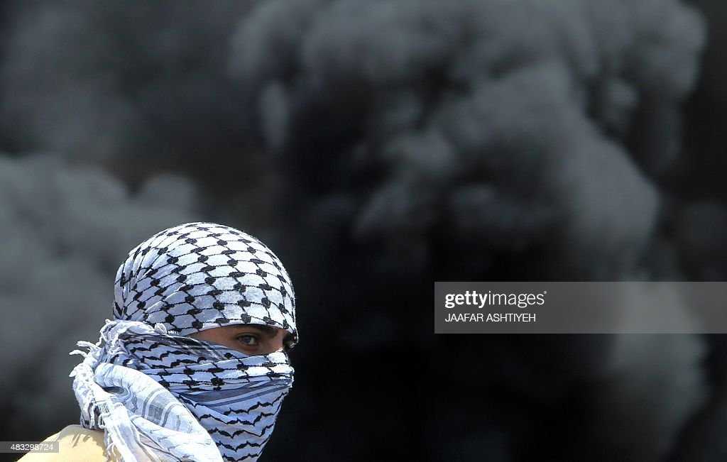 A masked Palestinian protester looks on amid the smoke of burning tires during clashes with Israeli security forces following a demonstration against...