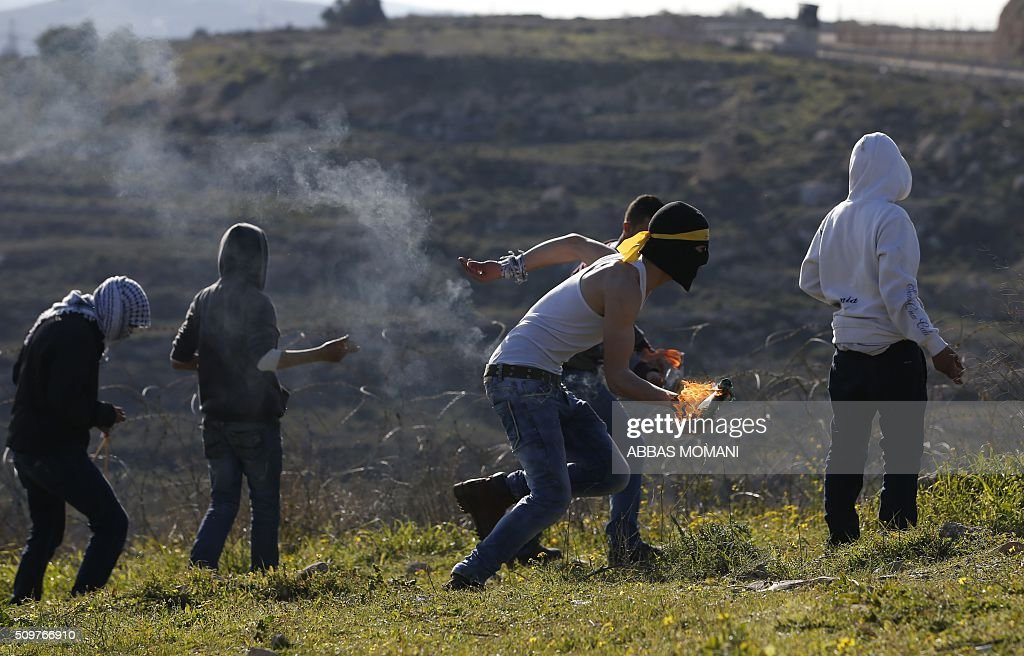 A masked Palestinian protester runs with a burning molotov cocktail during clashes with Israeli forces following a demonstration on February 12, 2016 in solidarity with Palestinian prisoners held in Israeli jails, outside the compound of the Israeli-run Ofer Prison near Betunia in the occoupied West Bank. / AFP / ABBAS MOMANI / AFP / ABBAS MOMANI