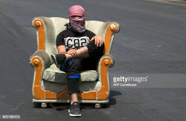 A masked Palestinian protester sits in an armchair along the road during a demonstration at the Hawara checkpoint south of Nablus in the...