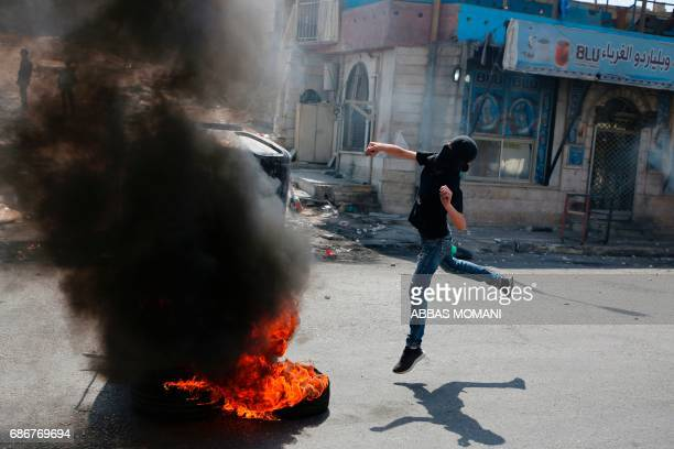 TOPSHOT A masked Palestinian protester throws a stone towards Israeli troops during a protest by Palestinians in support of prisoners refusing food...