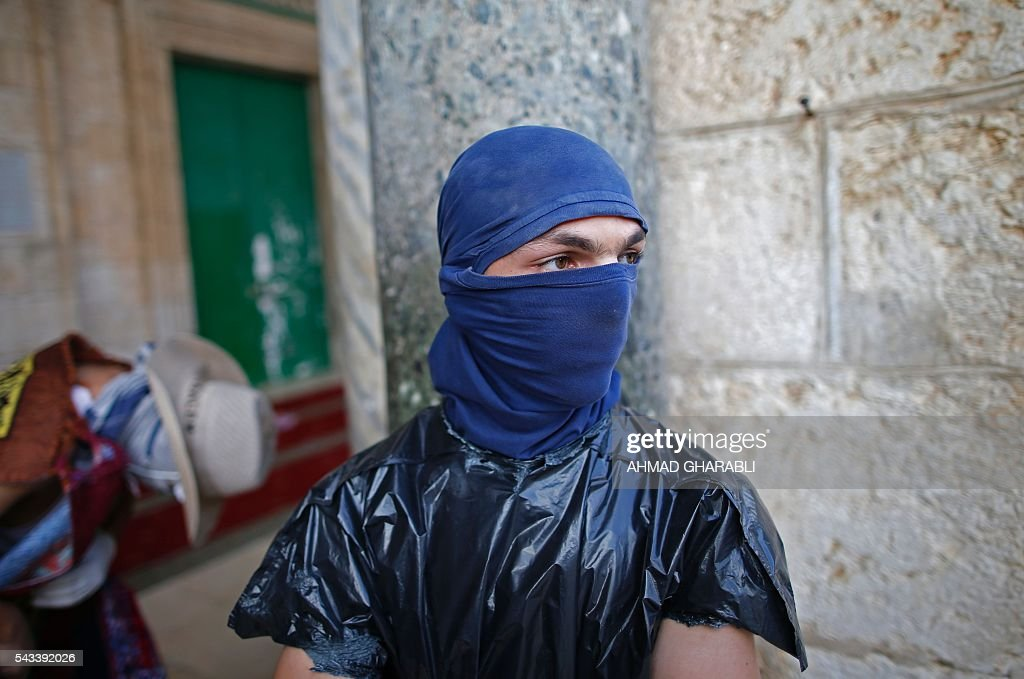 A masked Palestinian protester wearing a piece of plastic around his body stands during clashes with the Israeli police at Jerusalem's Al-Aqsa mosque compound for the thrid consecutive day on June 28, 2016 in Jerusalem's Old City . Israeli authorities announced they were closing Jerusalem's flashpoint Al-Aqsa mosque compound to non-Muslim visitors after a series of clashes between worshippers and police. The decision will apply until the end of the Muslim holy month of Ramadan next week. / AFP / AHMAD