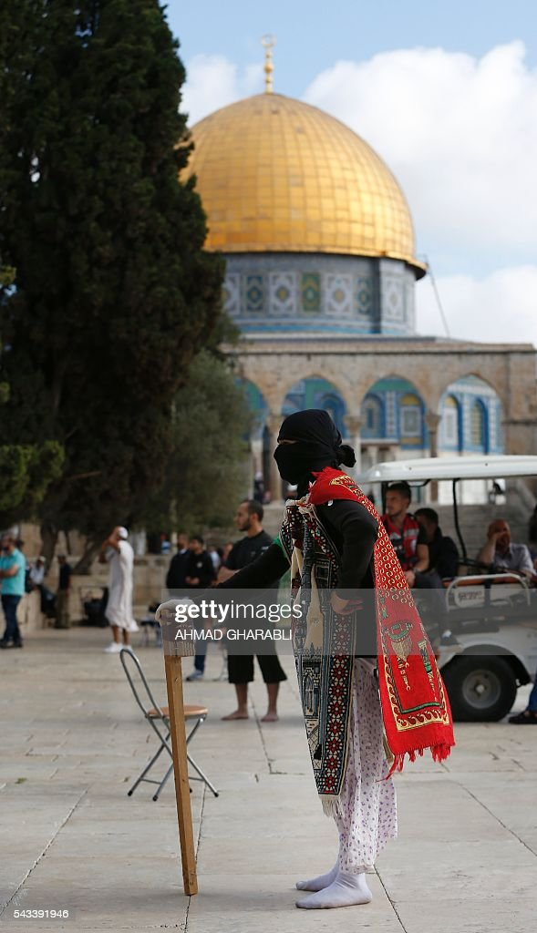 A masked Palestinian protester wearing pieces of cloth around his body keeps watch following clashes with Israeli police at Jerusalem's Al-Aqsa mosque compound for the thrid consecutive day on June 28, 2016 in Jerusalem's Old City. Israeli authorities announced they were closing Jerusalem's flashpoint Al-Aqsa mosque compound to non-Muslim visitors after a series of clashes between worshippers and police. The decision will apply until the end of the Muslim holy month of Ramadan next week. / AFP / AHMAD