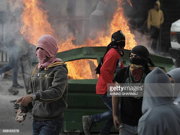 Masked Palestinian protesters clash with Israeli security forces in the Palestinian refugee camp of Shuafat in east Jerusalem on November 5 after a...
