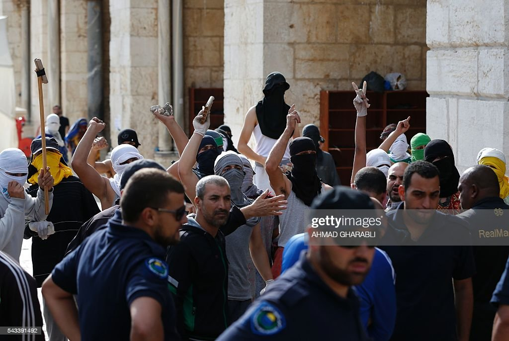 Masked Palestinian protesters gesture during clashes with the Israeli police at Jerusalem's Al-Aqsa mosque compound for the thrid consecutive day on June 28, 2016 in Jerusalem's Old City . Israeli authorities announced they were closing Jerusalem's flashpoint Al-Aqsa mosque compound to non-Muslim visitors after a series of clashes between worshippers and police. The decision will apply until the end of the Muslim holy month of Ramadan next week. / AFP / AHMAD
