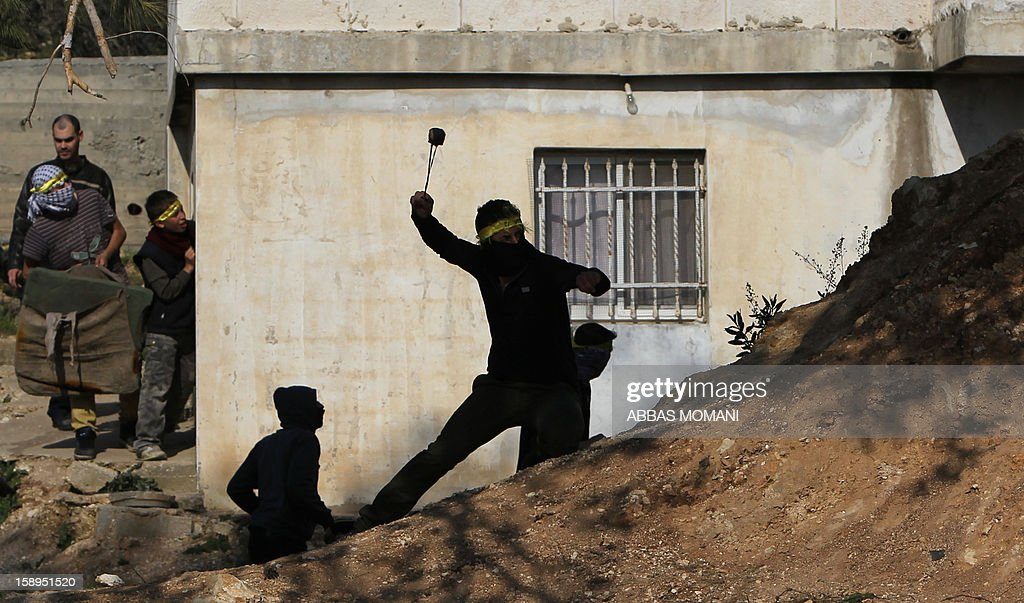 Masked Palestinian protesters hurl stones towards Israeli forces during clashes following a march organised by residents of the West Bank village Nabi Saleh to protest against the expansion of Jewish settlements on Palestinian land, on January 4, 2013 .