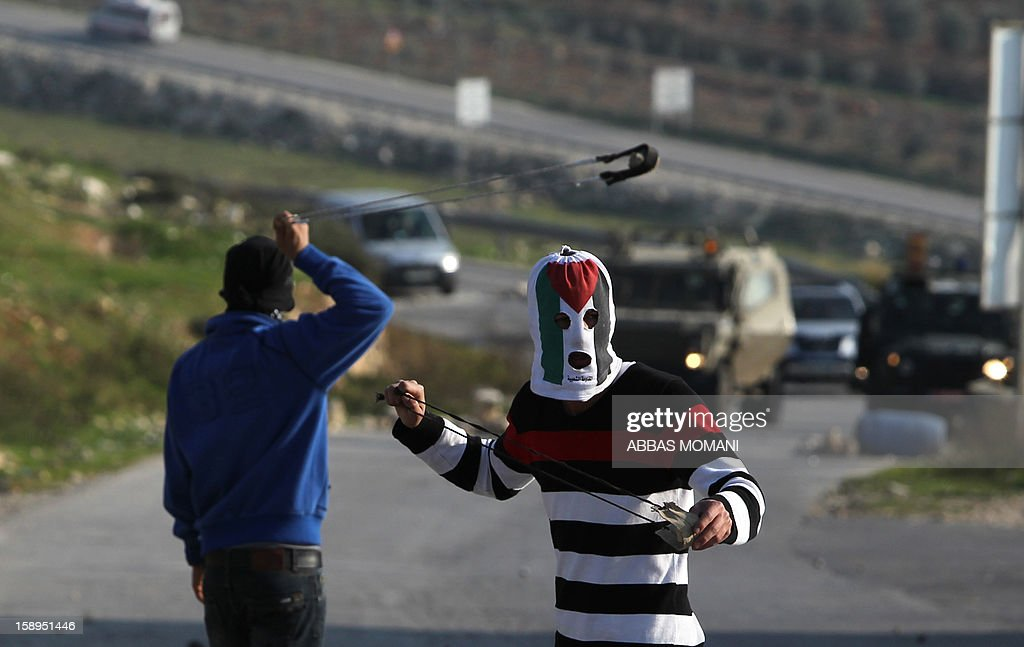 Masked Palestinian protesters prepare to hurl stones at Israeli forces during clashes following a march organised by residents of the West Bank village Nabi Saleh to protest against the expansion of Jewish settlements on Palestinian land, on January 4, 2013 . AFP PHOTO/ABBAS MOMANI