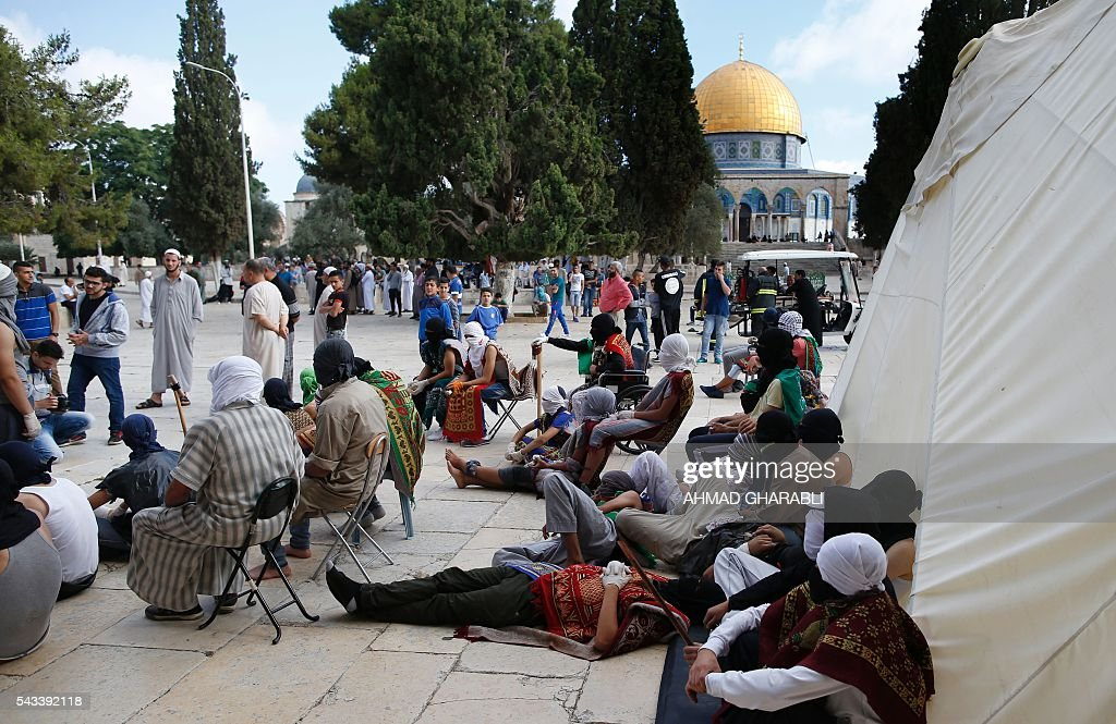 Masked Palestinian protesters rest following clashes with the Israeli police at Jerusalem's Al-Aqsa mosque compound for the thrid consecutive day on June 28, 2016 in Jerusalem's Old City . Israeli authorities announced they were closing Jerusalem's flashpoint Al-Aqsa mosque compound to non-Muslim visitors after a series of clashes between worshippers and police. The decision will apply until the end of the Muslim holy month of Ramadan next week. / AFP / AHMAD