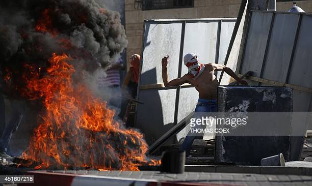 Masked Palestinian protesters throw stones towards Israeli police during clashes in the Shuafat neighborhood in Israeliannexed Arab East Jerusalem on...