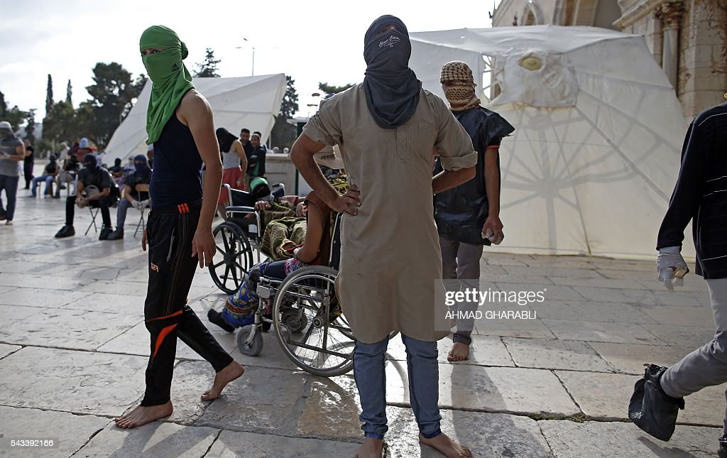 Masked Palestinian protesters wearing pieces of cloth and plastic around their bodies are seen during clashes with the Israeli police at Jerusalem's Al-Aqsa mosque compound for the thrid consecutive day on June 28, 2016 in Jerusalem's Old City. Israeli authorities announced they were closing Jerusalem's flashpoint Al-Aqsa mosque compound to non-Muslim visitors after a series of clashes between worshippers and police. The decision will apply until the end of the Muslim holy month of Ramadan next week. / AFP / AHMAD