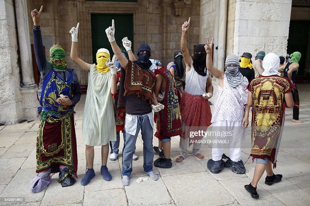 Masked Palestinian protesters wearing pieces of cloth around their bodies gesture during clashes with the Israeli police at Jerusalem's Al-Aqsa mosque compound for the thrid consecutive day on June 28, 2016 in Jerusalem's Old City . Israeli authorities announced they were closing Jerusalem's flashpoint Al-Aqsa mosque compound to non-Muslim visitors after a series of clashes between worshippers and police. The decision will apply until the end of the Muslim holy month of Ramadan next week. / AFP / AHMAD