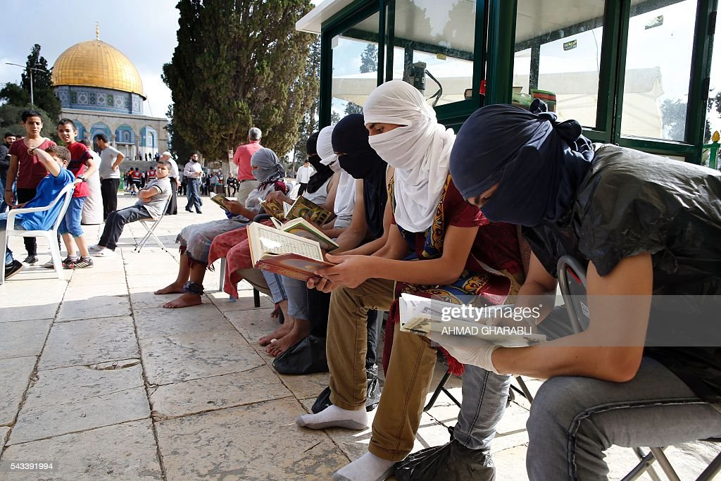 Masked Palestinian protesters wearing pieces of cloth around their bodies read the Koran following clashes with the Israeli police at Jerusalem's Al-Aqsa mosque compound for the thrid consecutive day on June 28, 2016 in Jerusalem's Old City . Israeli authorities announced they were closing Jerusalem's flashpoint Al-Aqsa mosque compound to non-Muslim visitors after a series of clashes between worshippers and police. The decision will apply until the end of the Muslim holy month of Ramadan next week. / AFP / AHMAD