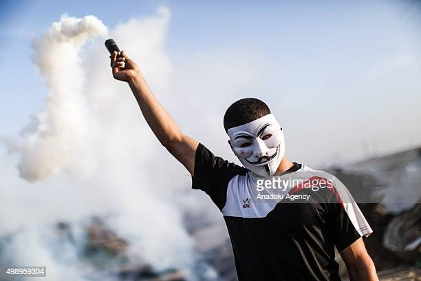 A masked Palestinian protestor holds a gas capsule in his hands during clashes along the border with Israel in Gaza City Gaza on November 27 2015
