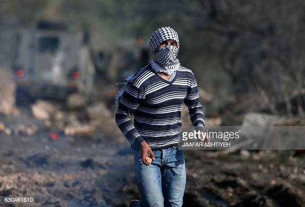 A masked Palestinian protestor holds a stone during clashes with Israeli security forces following a demonstration against the expropriation of...