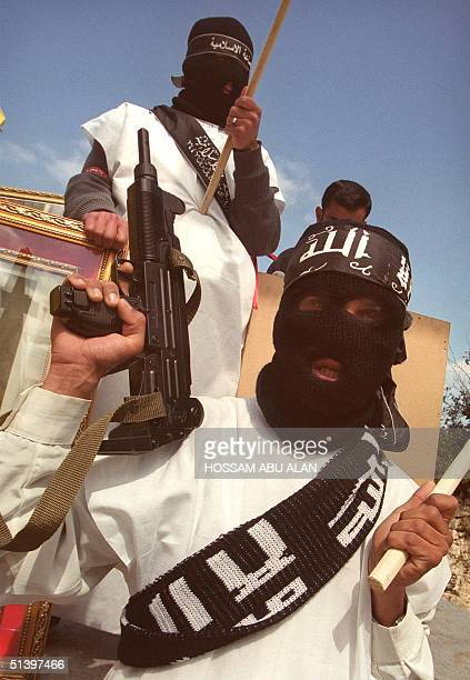 A masked Palestinian student of the Islamic Jihad movement which is violently opposed to the peace process with Israel waves an Uzi toy gun at the...