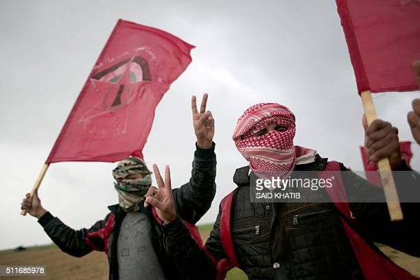 Masked Palestinian supporters of the Democratic Front for the Liberation of Palestine shout slogans and hold flags of the movement during an...