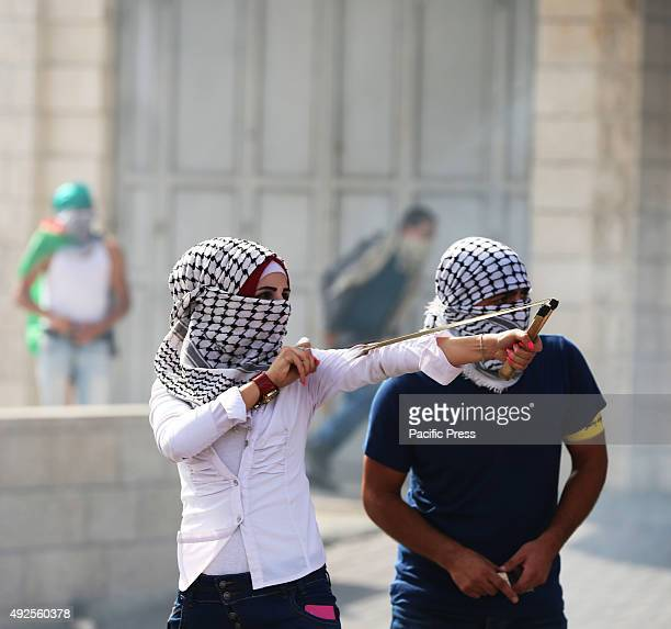 A masked Palestinian woman demonstrator uses a slingshot to hurl marbles at an Israeli military checkpoint in the West Bank city of Bethlehem A...