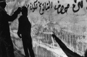 A masked Palestinian writes revolutionary graffiti on the wall of Arrura refugee camp on the West Bank during the IsraeliPalestinian conflict circa...