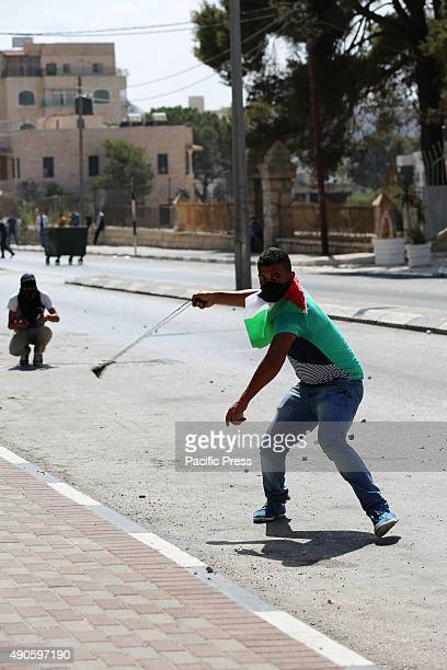 A masked Palestinian youth gets ready to hurl a rock at Israeli soldiers during a demonstration in the West Bank city of Bethlehem Palestinians in...