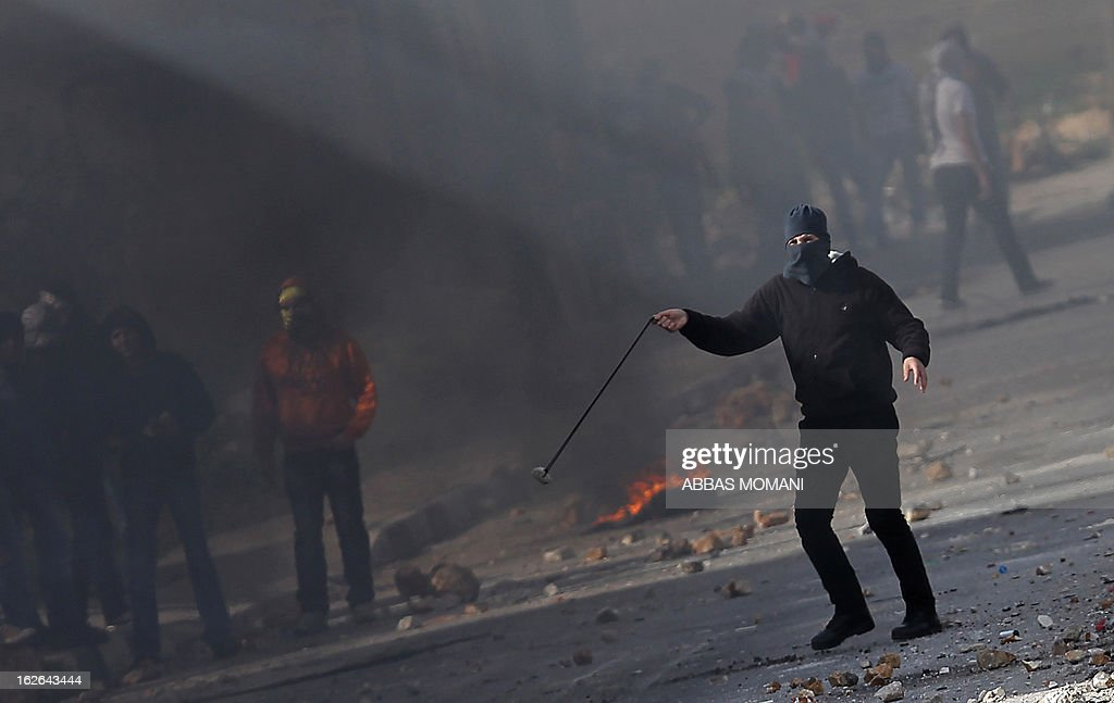 A masked Palestinian youth hurls a stone towards Israeli forces during clashes outside Israel's Ofer prison near Ramallah on February 25, 2013 after a protest in support of Palestinian prisoners on hunger strike in Israeli prisons. Palestinian president Mahmud Abbas said that Israel was deliberately seeking to stoke unrest in the occupied West Bank but that Palestinians would not be provoked. AFP PHOTO/ABBAS MOMANI