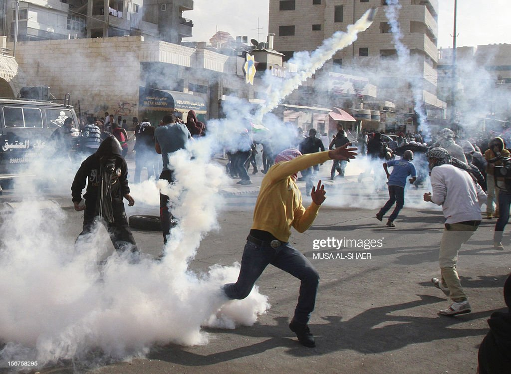 A masked Palestinian youth throws back a tear gas canister towards Israeli security forces (unseen) during clashes in the West Bank city of Bethlehem, on November 20, 2012. Palestinians clashed with Israeli security forces in the occupied West Bank as thousands marched demanding revenge for the killing of a protester the day before AFP PHOTO/MUSA AL-SHAER