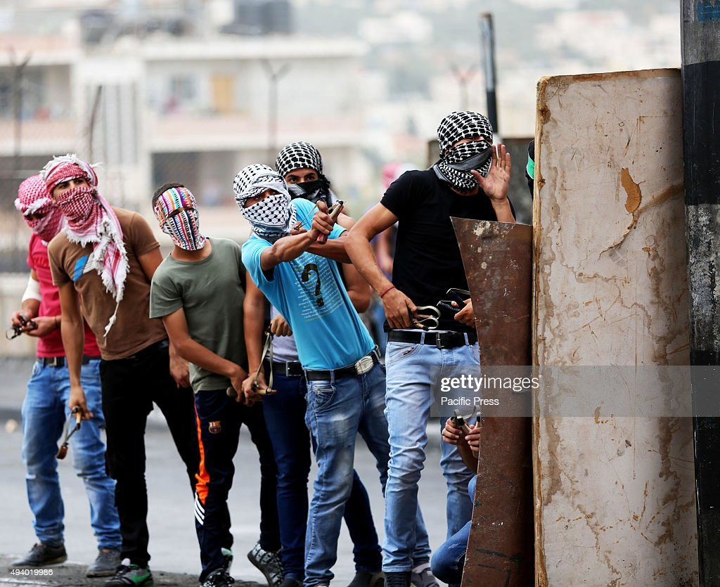 Masked Palestinian youth use slingshots to hurl rocks and marbles at an Israeli military checkpoint in Bethlehem West Bank Violent confrontations...