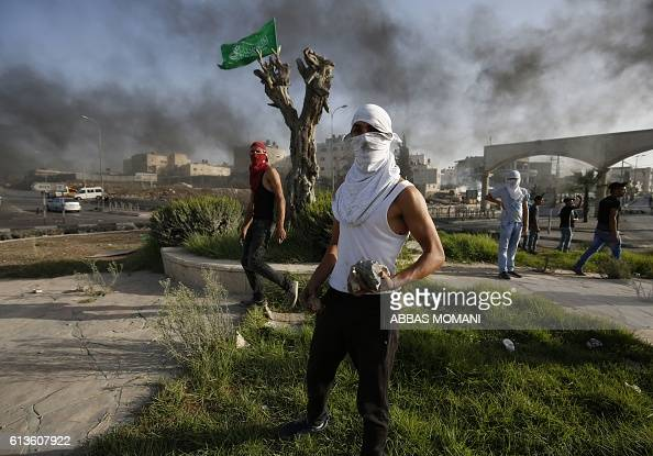 Masked Palestinian youths holding stones are seen after placing the Hamas flag on the trunk of a tree during clashes between Israeli security forces...