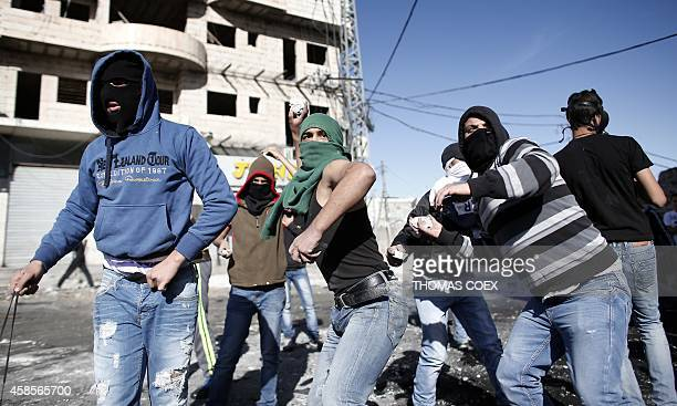 Masked Palestinian youths throw stones during clashes with Israeli security forces in the Palestinian refugee camp of Shuafat in east Jerusalem on...