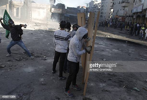Masked Palestinian youths use doors as shields during clashes with Israeli security forces in the Palestinian refugee camp of Shuafat in east...